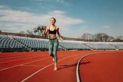 A beautiful young mixed race girl is running along a treadmill at the stadium. The concept of a healthy lifestyle and losing weight royalty free stock images