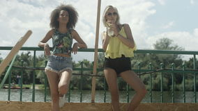 Beautiful young mixed race girls standing near a lake talking, drinking and having good time. stock footage