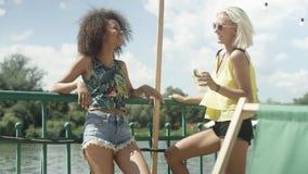 Beautiful young mixed race girls talking near lake and enjoying vacation. Royalty Free Stock Images