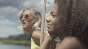 Beautiful young mixed race girls talking near lake and having great time. Young beautiful mixed race girls enjoying vacation. Summer/vacation concept stock video footage