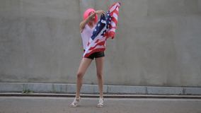 Beautiful young mixed race woman in pink wig with American flag at city street.  stock footage
