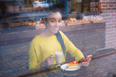 Beautiful young mixed race woman seen through the window of bakery Royalty Free Stock Photography