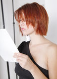 Beautiful young model and actress reads script. Beautiful young redhead female model and actress looks over script Royalty Free Stock Photos