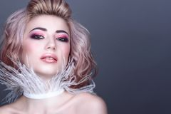 Beautiful young model with creative colorful make up and wavy hairstyle wearing stylish white feather collar stock image