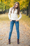 Beautiful young model dressed for chilly weather. Beautiful young model dressed for chilly weather posing outdoors in the park royalty free stock image