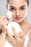 Beautiful young model holding a compact powder and applying some Royalty Free Stock Image