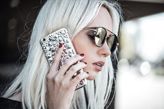 Beautiful young model with phone outdoor Stock Photography