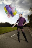Nice lady posing with balloons. Beautiful young model posing with set of balloons on location of city park royalty free stock photo