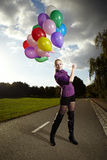Balloon fashion. Beautiful young model posing with set of balloons on location of city park stock image