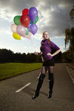 Nice lady posing on sidewalk. Beautiful young model posing with set of balloons on location of city park stock photos