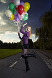 Beauty in park with balloons. Beautiful young model posing with set of balloons on location of city park stock images