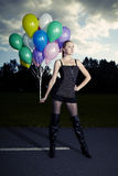 Posing in dark. Beautiful young model posing with set of balloons on location of city park stock photo