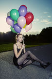 Posing in park on ground. Beautiful young model posing with set of balloons on location of city park royalty free stock images