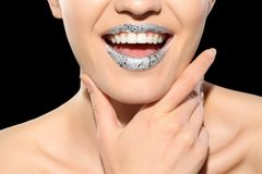 Beautiful model with silver lips makeup on black background. Beautiful young model with silver lips makeup on black background royalty free stock photography