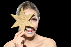 Beautiful young model with silver lips makeup star on black background. Beautiful young model with silver lips makeup and star on black background stock photo
