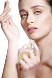Beautiful young model spraying a flowers fragrance on her body. On white Royalty Free Stock Image