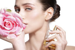 Beautiful young model spraying a flowers fragrance on her body stock photo
