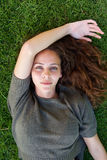 Beautiful young model staring while lying on grass Stock Images
