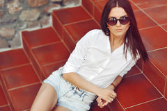Beautiful young model in sunglasses posing outdoor Stock Photo