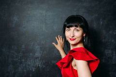 Beautiful young model woman in red dress posing over black slate Royalty Free Stock Image