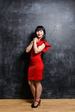 Beautiful young model woman in red dress posing over black slate Stock Images