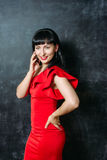 Beautiful young model woman in red dress posing over black slate Royalty Free Stock Photo