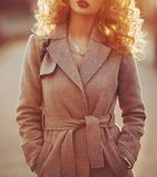 Beautiful young modern woman smiling happy and cheerful in trench coat. Beautiful young modern woman smiling happy and cheerful in trench coat royalty free stock photos