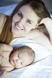 Beautiful Young Mom. Lying with her newborn baby Stock Images