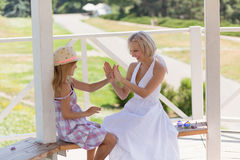 Beautiful young mom and daughter playing with hands. Woman and girl sittng in shadow at summer house on a hot sunny day Royalty Free Stock Photo