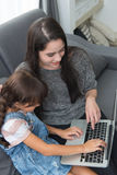 Beautiful young mom and daughter are using notebook on sofa at h Stock Image