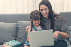 Beautiful young mom and daughter are using notebook on sofa at h Stock Photo