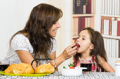 Beautiful young mom feeding fruit to cute little Royalty Free Stock Photos