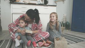 Beautiful young mom and her cute little daughter are playing with cookie cutters and smiling while baking in kitchen at stock video footage