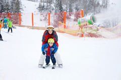 Beautiful young mom and her toddler boy, skiing in the mountains Royalty Free Stock Image