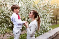 Beautiful young mom holding hands with little son outdoors. In the summer stock images