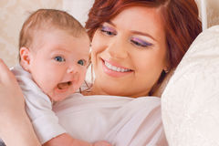 Beautiful young mom that keeps her child in her arms, lying on t Royalty Free Stock Images