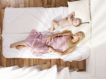 Beautiful young mom with naked baby. Photos of a beautiful young mother with a naked child in bed Royalty Free Stock Image