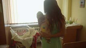 Young mom with newborn baby in her arms stock video