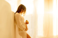 Beautiful young mom to be, leaning on a wall, holding little duc. Klings in the early morning light, back light coming through the window Royalty Free Stock Photo