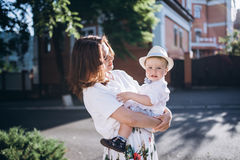 Beautiful young momhold their son. Woman look to the son, they are both feel happy.  stock photos