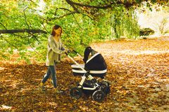 Beautiful mother with baby carriage walking in autumn park. Royalty Free Stock Images