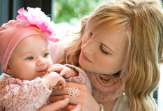 Beautiful young mother with baby daughter. Beautiful young mother with her baby daughter royalty free stock images