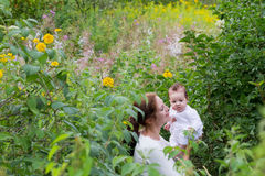 Beautiful young mother with a baby girl in flower field. Beautiful young mother with a baby girl in pink flower field royalty free stock photos