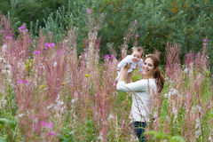 Beautiful young mother with a baby girl in flower field. Beautiful young mother with a baby girl in pink flower field Stock Photography