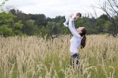 Beautiful young mother with a baby girl in flower field Royalty Free Stock Images