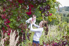 Beautiful young mother with a baby girl in flower field Royalty Free Stock Photography