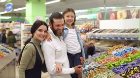 A beautiful young mother with a bearded husband and a cute daughter buy candies. A beautiful young mother with a bearded husband and a cute seven-year-old stock video