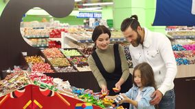 Happy parents with a little daughter buy chocolates in a candy store. A beautiful young mother with a bearded husband and a cute seven-year-old daughter buy stock footage