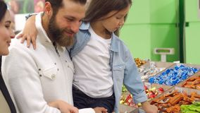 Young parents buy candy for their daughter in the supermarket. A beautiful young mother with a bearded husband and a cute seven-year-old daughter buy chocolate stock video footage