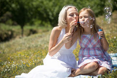 Beautiful young mother blowing bubbles with her daughter. Mom and child enjoying picnic outdoors stock photography
